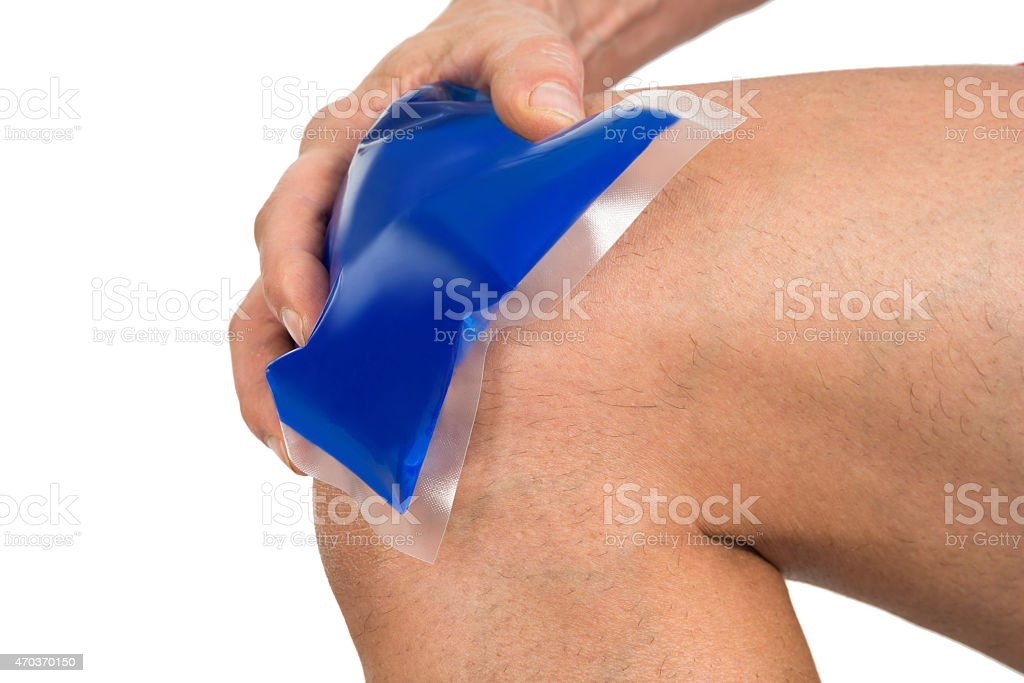 Hand Holding Ice Gel Pack On Knee stock photo