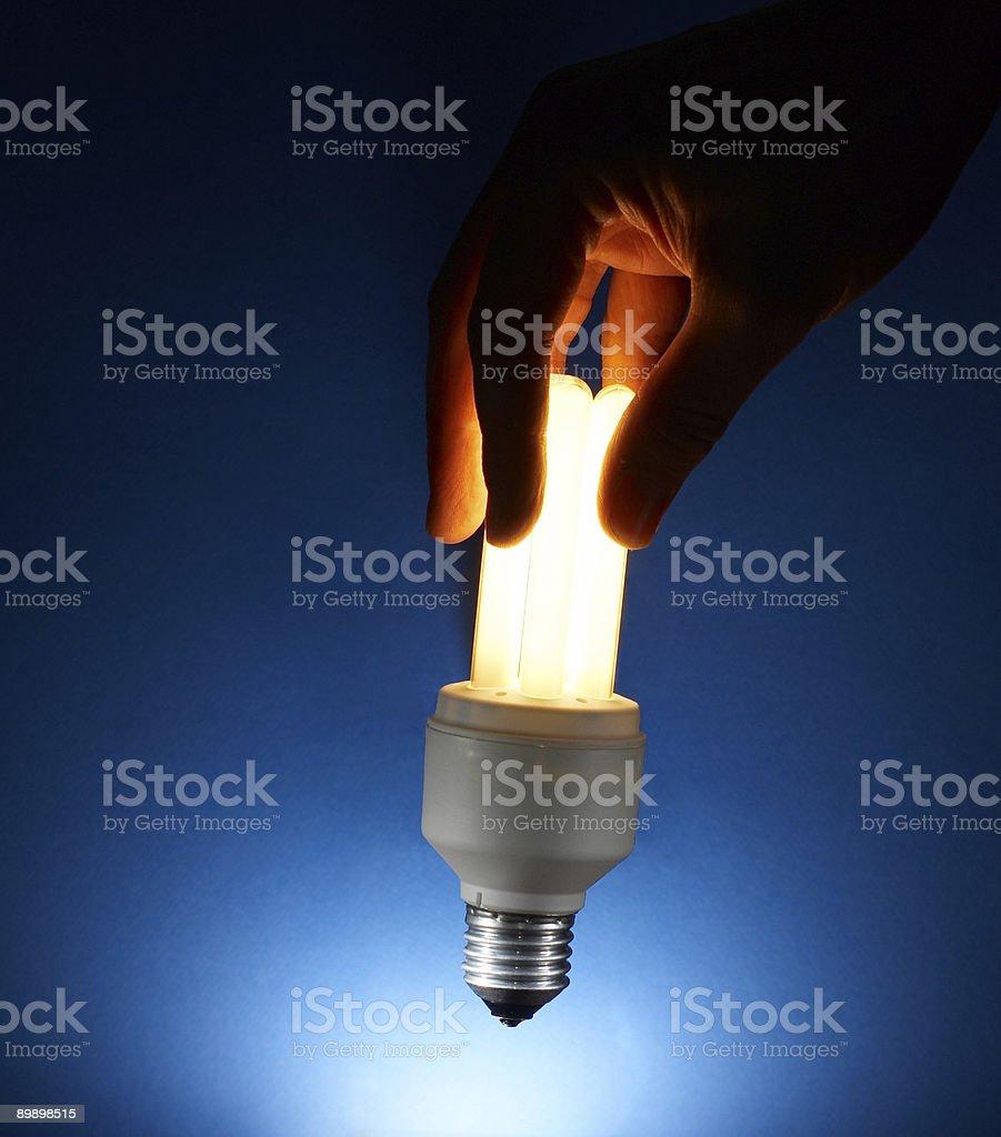 Hand holding illuminated Compact Fluorescent light bulb without socket stock photo