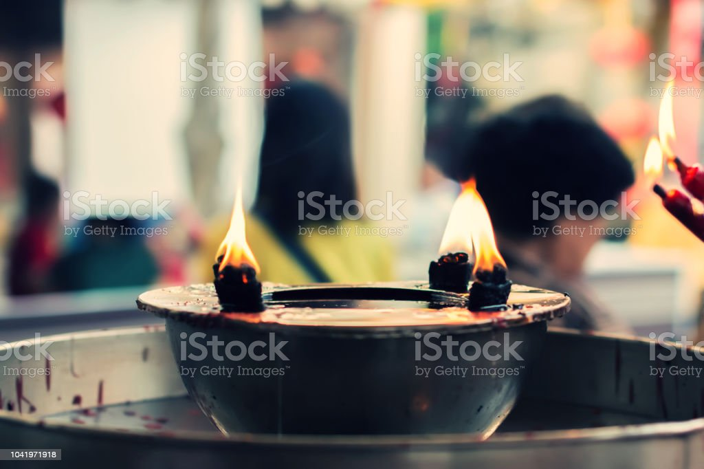 Hand Holding Incense Stick Burning By Candle For Praying In