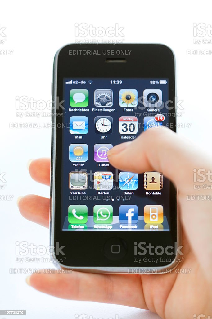 hand holding iPhone 3 typing on home screen royalty-free stock photo