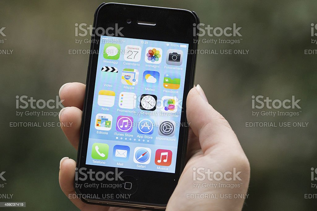 Hand Holding Iphone 4s with iOS 7 on stock photo