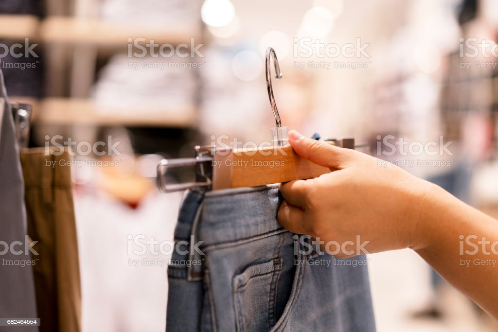 hand holding jeans in shop royalty-free stock photo
