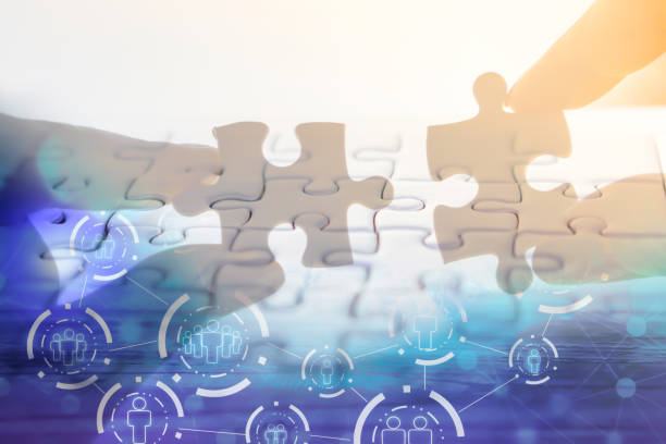 hand holding jigsaw piece with background of teamwork people connection hand holding jigsaw piece with background of teamwork people connection ,business success concept jigsaw piece stock pictures, royalty-free photos & images