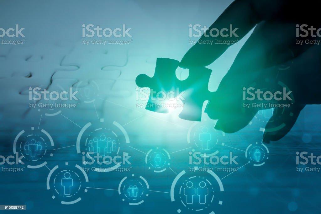 Hand hält Puzzleteil mit Hintergrund der Teamarbeit – Foto
