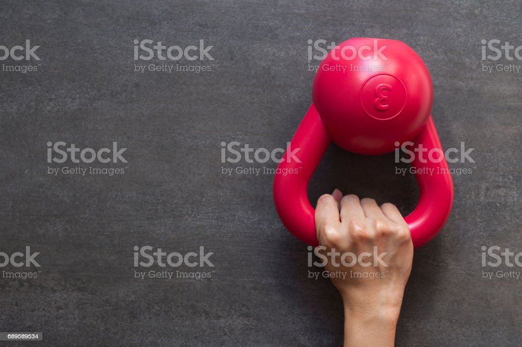 Hand holding kettlebell on a black background stock photo