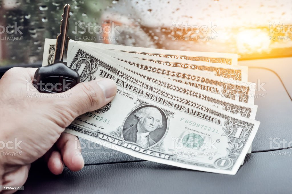 Hand holding Key of car on road and  dollar money for everyday shopping vintage stock photo