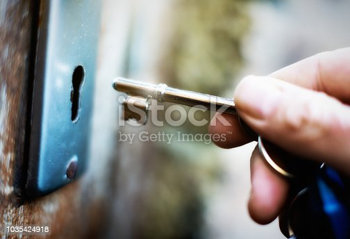 A hand holds a key on  a key ring, about to lock or unlock an old wooden door.