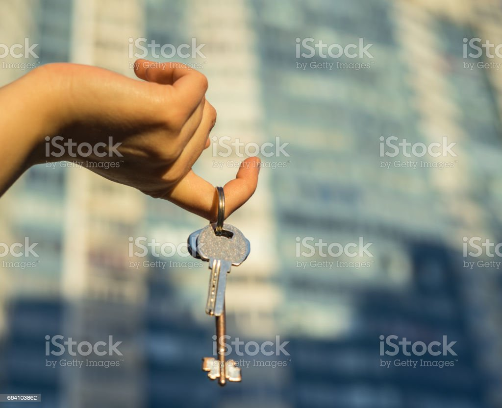 Hand holding key with modern building on background. foto stock royalty-free