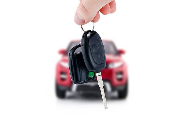 Hand holding keys to new car Hand holding keys to new red car. Buy or selling business composition car key stock pictures, royalty-free photos & images