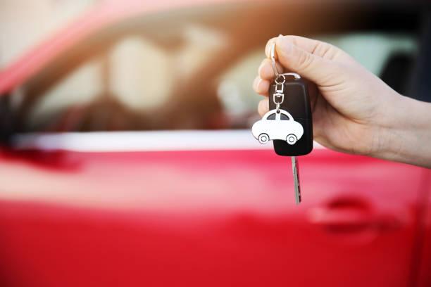 Hand holding keys to new car stock photo