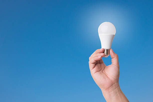 hand holding led bulb with lighting on blue sky background. - changing bulb led bildbanksfoton och bilder