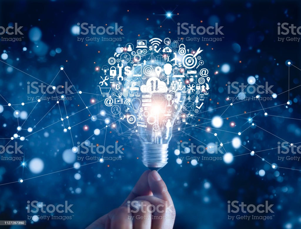 Hand holding light bulb and business digital marketing innovation technology icons on network connection, blue background - Foto stock royalty-free di Affari