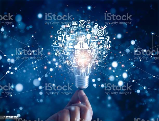 Hand Holding Light Bulb And Business Digital Marketing Innovation Technology Icons On Network Connection Blue Background Stock Photo - Download Image Now