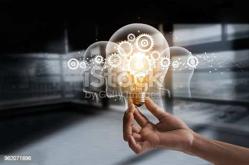 istock Hand holding light bulb and cog inside. Idea and imagination. Creative and inspiration. Innovation gears icon with network connection on human heads on metal texture background. Innovative technology in science and industrial concept 962071696