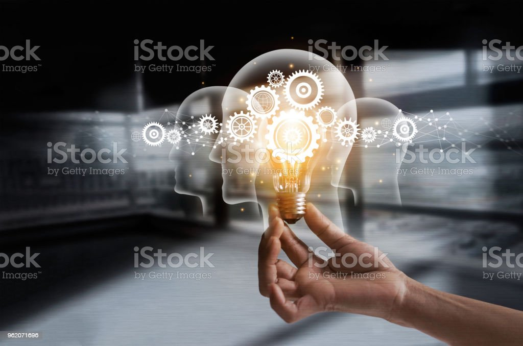 Hand holding light bulb and cog inside. Idea and imagination. Creative and inspiration. Innovation gears icon with network connection on human heads on metal texture background. Innovative technology in science and industrial concept stock photo