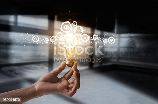 istock Hand holding light bulb and cog inside. Idea and imagination. Creative and inspiration. Innovation gears icon with network connection on metal texture background. Innovative technology in science and industrial concept 962094570