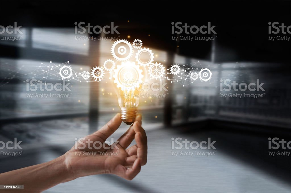 Hand holding light bulb and cog inside. Idea and imagination. Creative and inspiration. Innovation gears icon with network connection on metal texture background. Innovative technology in science and industrial concept stock photo
