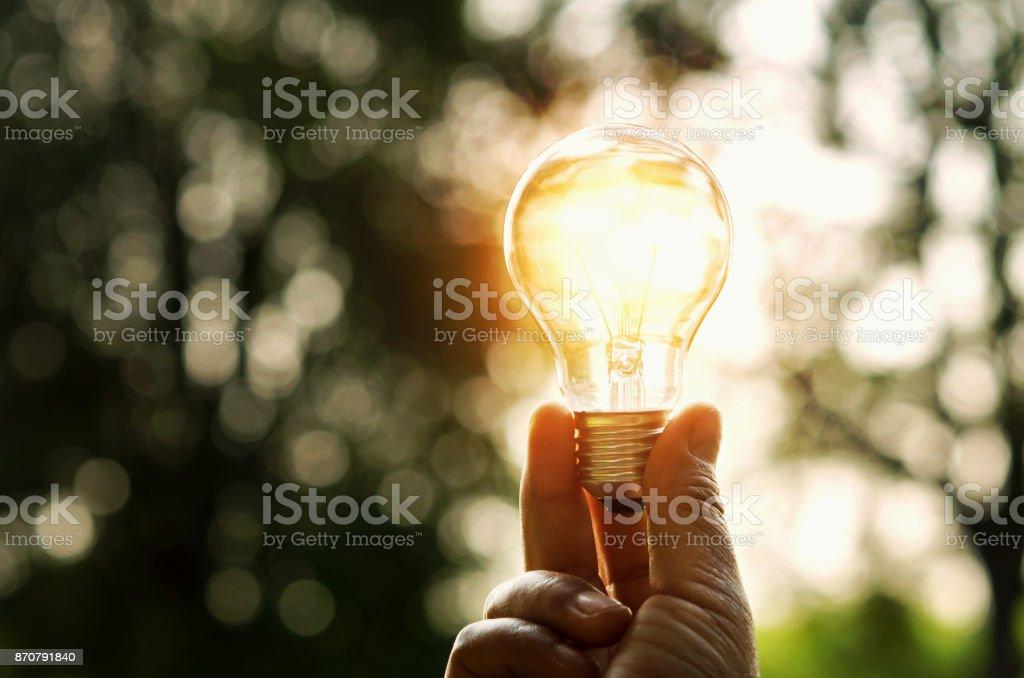 Hand mit Glühbirne und Sonnenuntergang in der Natur, macht Energiekonzept Lizenzfreies stock-foto