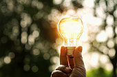 istock hand holding light bulb and sunset in nature, power energy concept 870791840