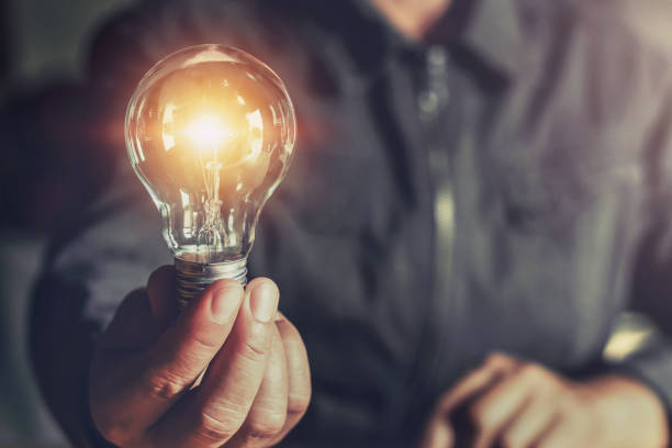 hand holding light bulb. idea concept with innovation and inspiration - light bulb stock pictures, royalty-free photos & images