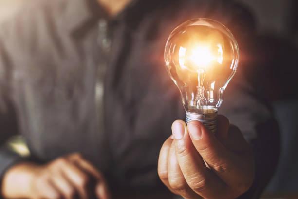 Hand hält Glühbirne. Ideenkonzept mit Innovation und Inspiration – Foto