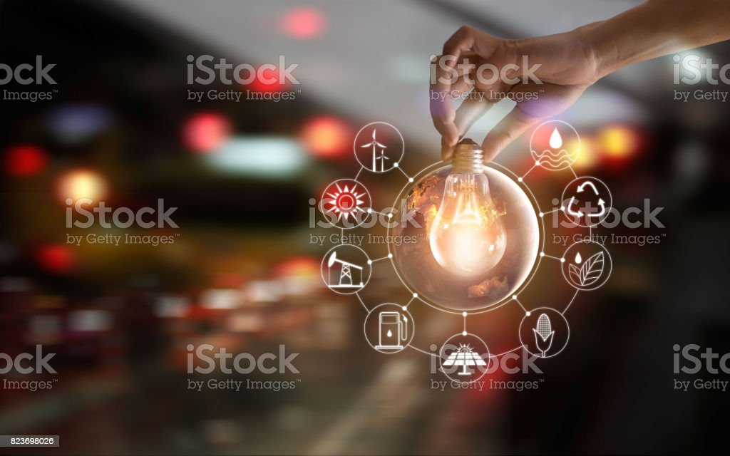 Hand holding light bulb in front of global show the world's consumption with icons energy sources for renewable, sustainable development. Ecology and environment concept. stock photo