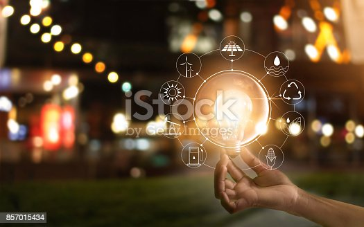istock Hand holding light bulb in front of global show the world's consumption with icons energy sources for renewable, sustainable development. Ecology concept 857015434