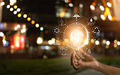 Hand holding light bulb in front of global show the world's consumption with icons energy sources for renewable, sustainable development. Ecology concept
