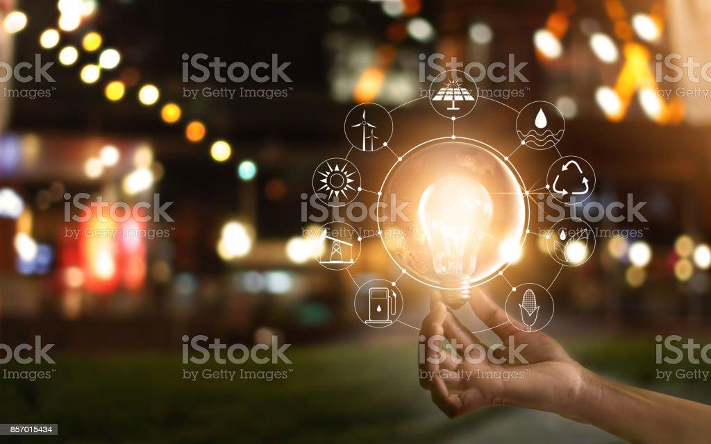 Mão segurando lâmpada na frente do programa global de consumo do mundo, com fontes de energia de ícones para o desenvolvimento sustentável, renovável. Conceito de ecologia - foto de acervo