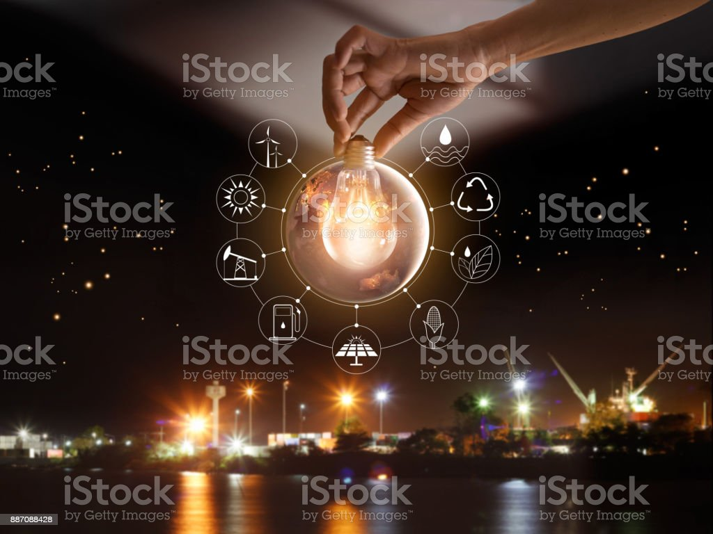 Hand holding light bulb in front of global show the world's consumption with icons energy sources for renewable, sustainable development. Ecology concept. Elements of this image furnished by NASA. stock photo