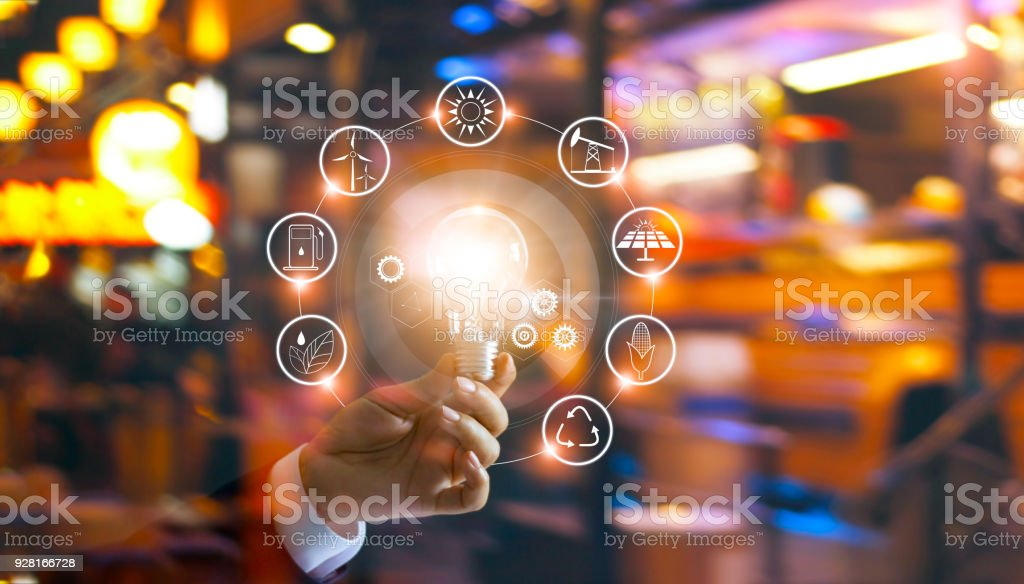 Hand holding light bulb in front of global show the world's consumption with icons energy sources for renewable, sustainable development. Ecology concept. stock photo