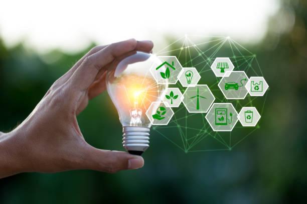 再生可能のためのアイコンのエネルギー源を持つ手持ち電球は、世界のコンセプトを愛する。 - sustainability ストックフォトと画像