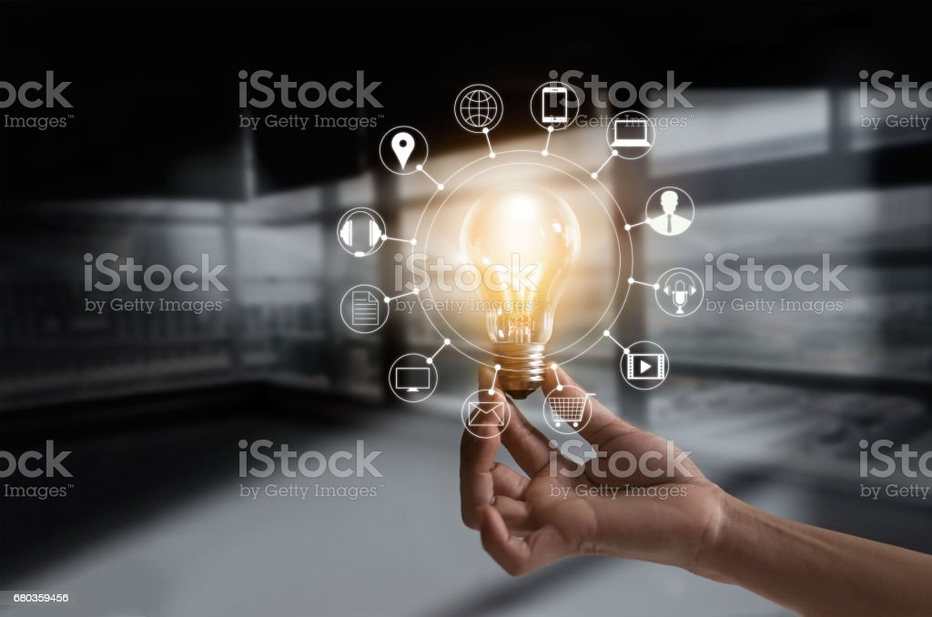Hand holding light bulb with icons multimedia and customer network connection on dark room background stock photo