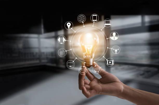 暗い部屋の背景にマルチ メディアと顧客のネットワーク接続アイコンと電球を持っている手 ストックフォト