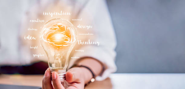 Hand holding light bulb with innovation and creativity are keys to success. Concept knowledge leads to ideas and inspiration. stock photo