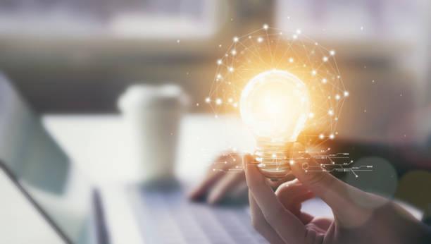 ręczne trzymanie żarówki z innowacyjnością i kreatywnością to klucz do sukcesu. wiedza koncepcyjna prowadzi do pomysłów i inspiracji. - natchnienie zdjęcia i obrazy z banku zdjęć