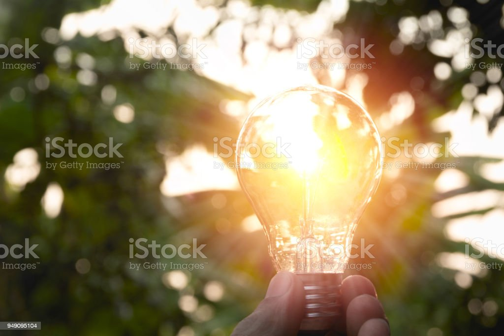 Hand, die Glühbirnen mit glühenden auf Boden. Idee, Kreativität und Energie sparen mit Glühbirnen Konzept. – Foto