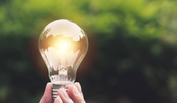 自然の背景に輝くと電球を持っている手。アイデア、創造性と概念の電球で省エネ。 - 電気部品 ストックフォトと画像