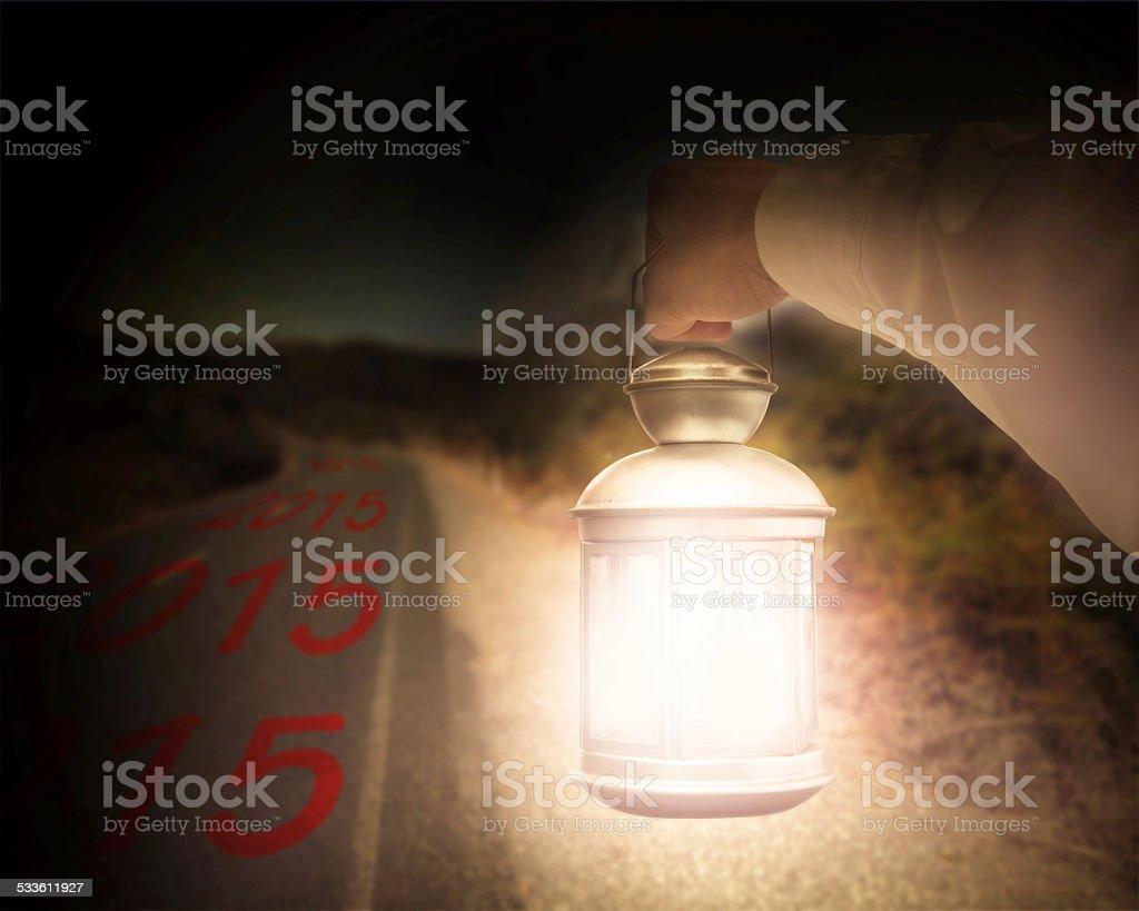 Hand holding light illuminating 2015 on dark road at night stock photo