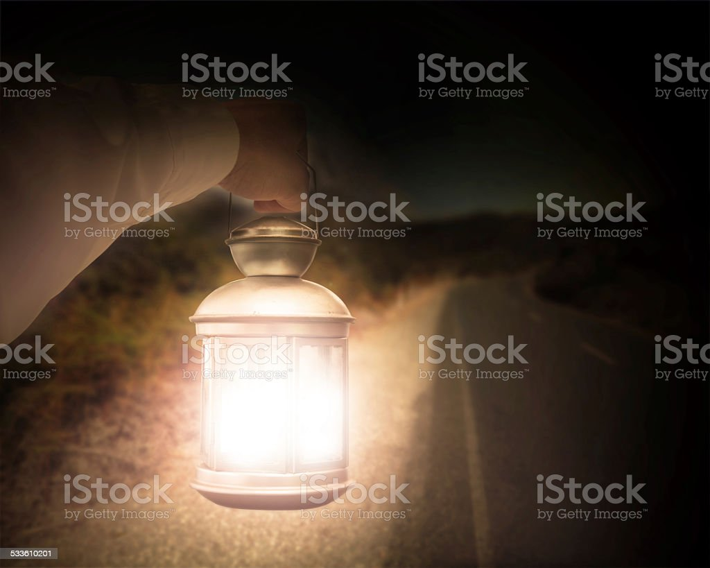 Hand holding light illuminating dark road at night stock photo