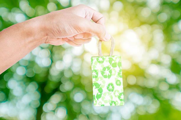 hand hält kleine päckchen grüne recycling-papier tasche - eco bastelarbeiten stock-fotos und bilder