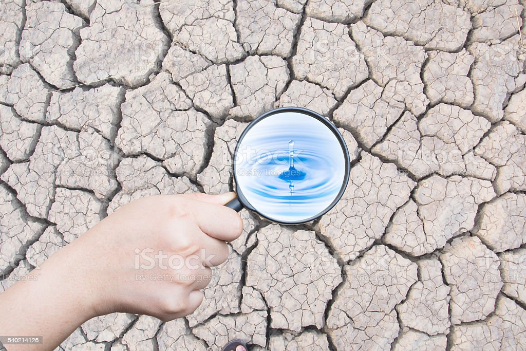 hand holding magnifying find water drop stock photo
