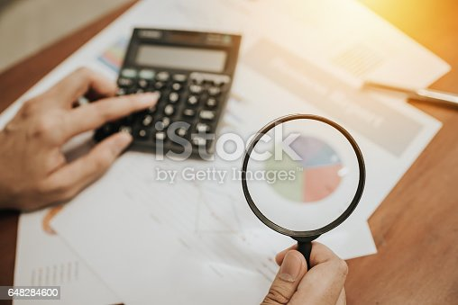 istock hand holding magnifying glass analyzing business 648284600