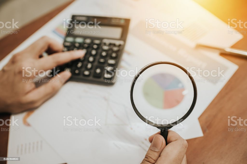 hand holding magnifying glass analyzing business stock photo