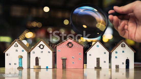 Hand holding magnifying glass and looking at house model, house selection, real estate concept.