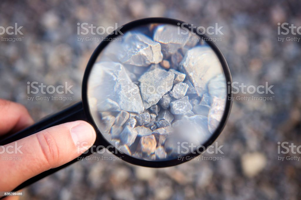 hand holding magnifying glass at stones royalty-free stock photo