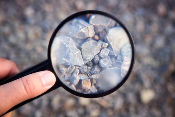 ręka trzymająca szkło powiększające przy kamieniach - geologia zdjęcia i obrazy z banku zdjęć