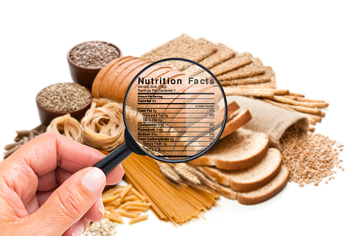 Close up view of a female hand holding magnifying glass on a group of carbohydrates food to look for the details of the nutrition facts of this type of food. A Nutrition Facts label is visible on the magnifying glass.