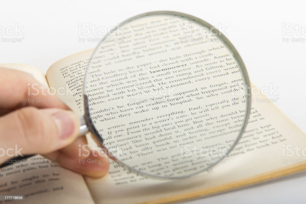 Hand Holding Magnifying Glass on Novel royalty-free stock photo