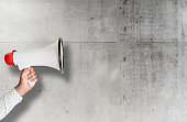 istock hand holding megaphone against rough concrete wall 1149062483
